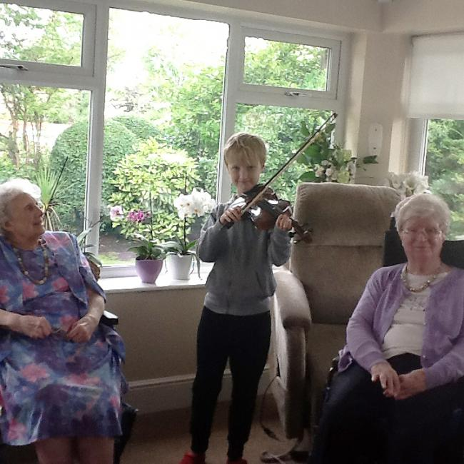 Young violinist Oscar White, 10, performs for residents of Wyncourt Nursing Home in Timperley