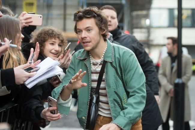 Harry Styles speaks with fans as he leaves Wogan House in London