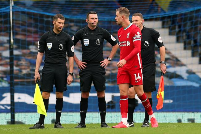 Liverpool captain Jordan Henderson speaks to referee Michael Oliver after the match