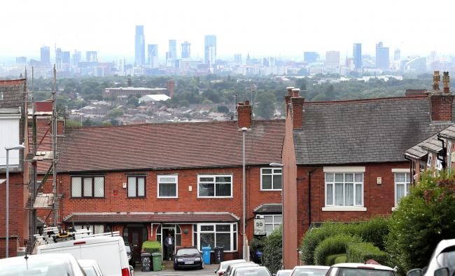 A Resident in Oldham stands in his doorway with the Manchester skyline behind, the town in Greater Manchester has seen cases of coronavirus rise in the area..