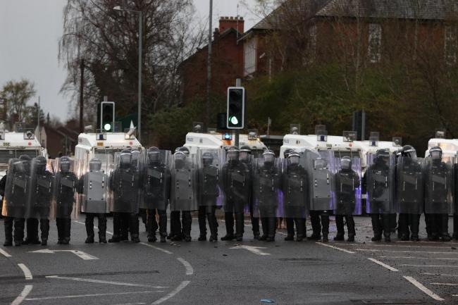 PSNI officers with riot shields line the Springfield road, during further unrest in Belfast
