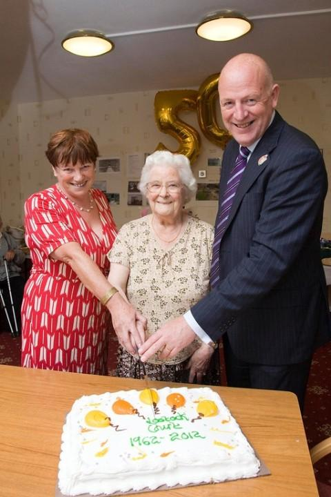 The longest resident, Ada Goodman, cuts the cake with Trust Chief-executive, Matthew Gardiner and Elaine Leary
