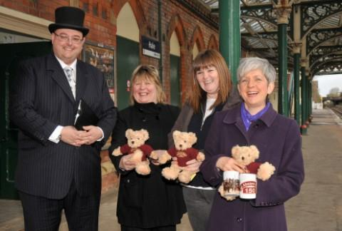 All aboard for Hale 150 - last year's celebration.Richard Blamire, Hale Civic Society chairman Denise Laver, Joanne Blinkhorn and Alison Barnett - with commemoration mugs and 'Henry' the railway bear