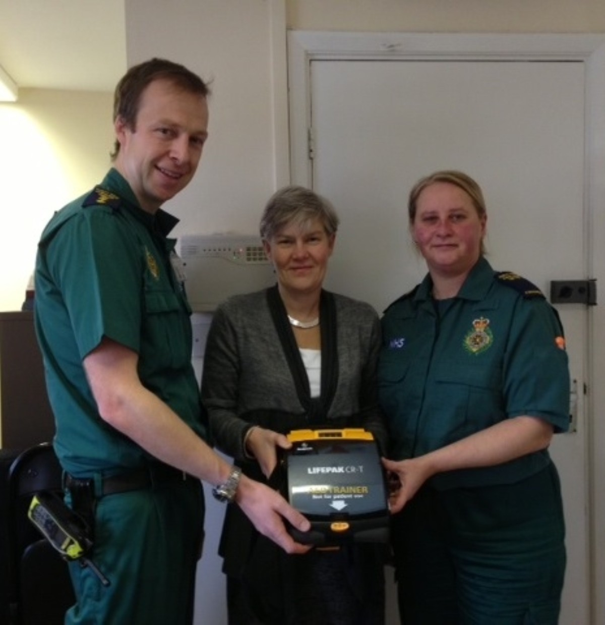 Kate Green MP holding a defibrillator with senior paramedic and community resuscitation manager, David McNally, and his colleague Lisa, both from the North West Ambulance Service NHS Trust