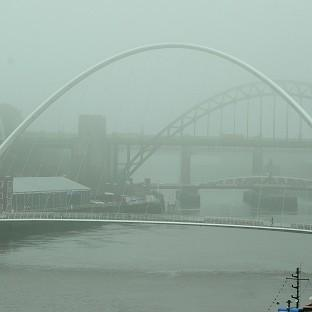 Messenger Newspapers: People walk through fog to cross the Tyne Bridge in Newcastle upon Tyne.