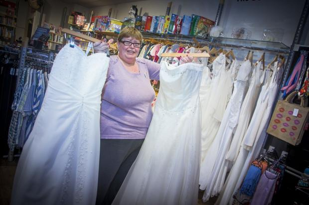 Manager Ann Long is pictured with the wedding dress windfall at the BHF shop in Stretford Mall