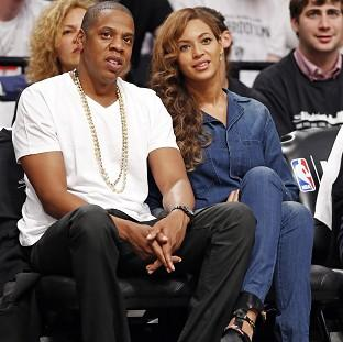 Messenger Newspapers: Jay-Z and his wife Beyonce, watching a basketball game in New York, hours after the video leak (AP)