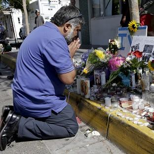 Jose Cardoso pays his respects at a makeshift memorial in front of the IV Deli Mart, where part of Friday night's mass shooting took place (AP)