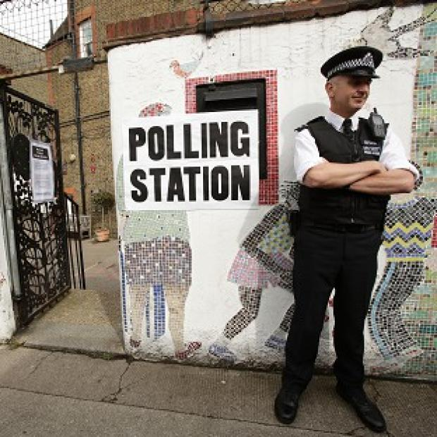 Messenger Newspapers: A police officer outside a polling station in Tower Hamlets