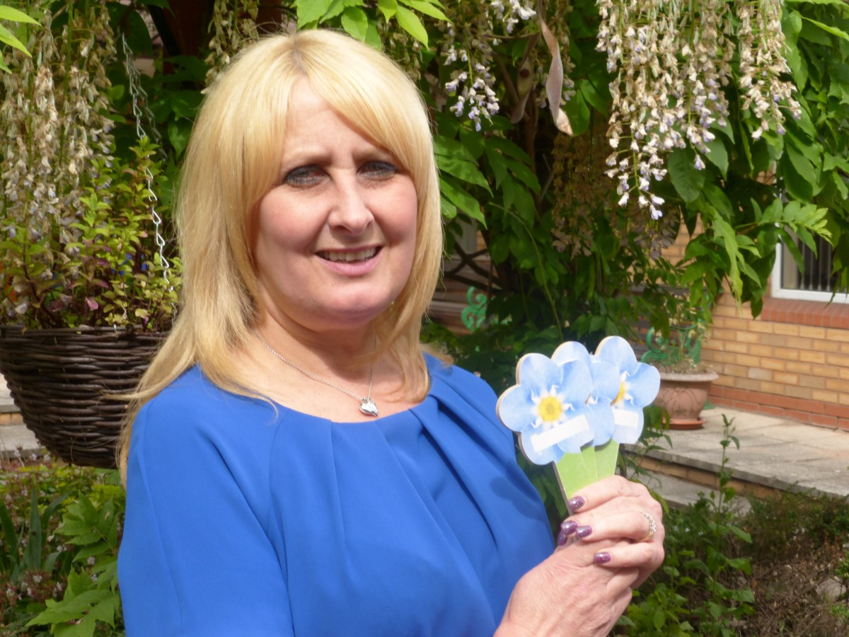 Jacqui Cook with the forget-me-not flowers