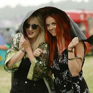 Messenger Newspapers: Festival goers during a rain shower at the Glastonbury Festival, at Worthy Farm in Somerset