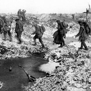 British soldiers negotiating a shell-cratered landscape in 1916