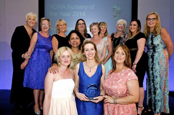 Photo shows NDNA Nursery Awards host, original Calendar Girl Tricia Stewart, Purnima Tanuku NDNA chief executive, and Sara Carr, chairman of trustees at NDNA, together with Roisin Moriarty (director, Oakfield Nursery School Ltd) holding the award