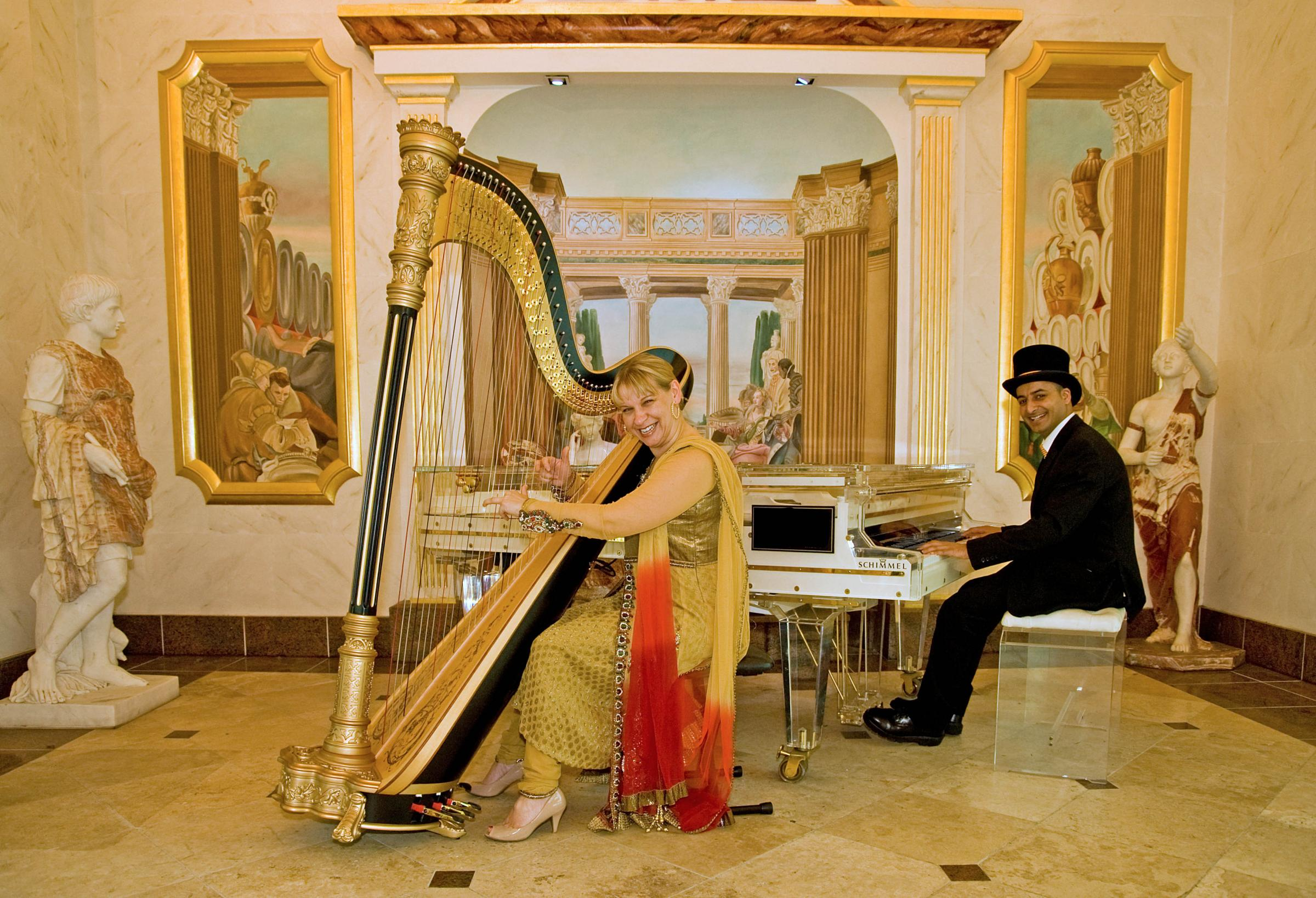 Wasim Awan, customer services, strikes up a welcome tune at the glass piano with Bollywood harpist Maxine Molin-Rose, who will be one