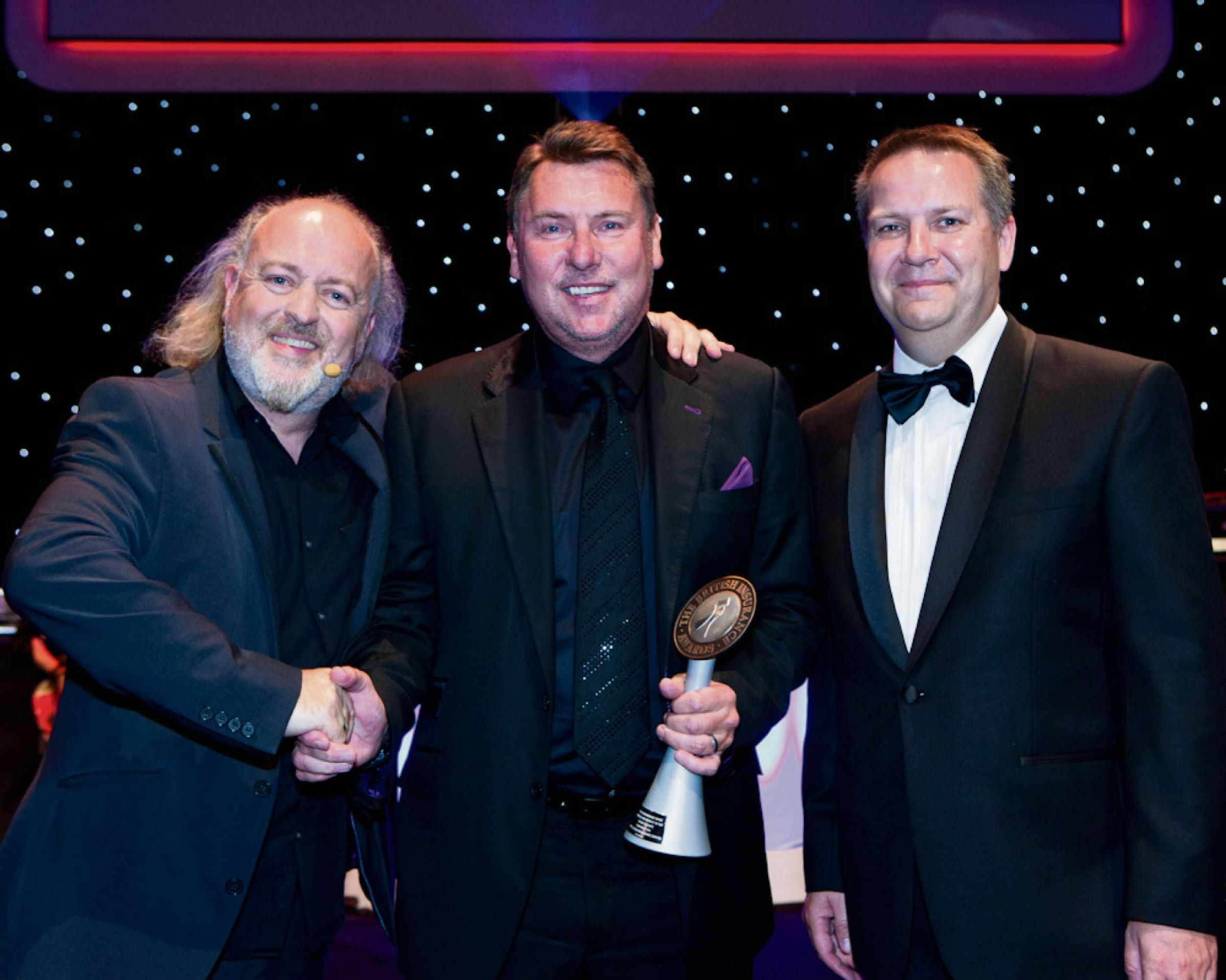 Paul Moors, centre, with the commercial lines broker of the year trophy flanked by Paul Hirst, right, a director at award sponsor RSA, and comedian Bill Bailey, left, who hosted the awards ceremony. Picture credit: Rob Kennard