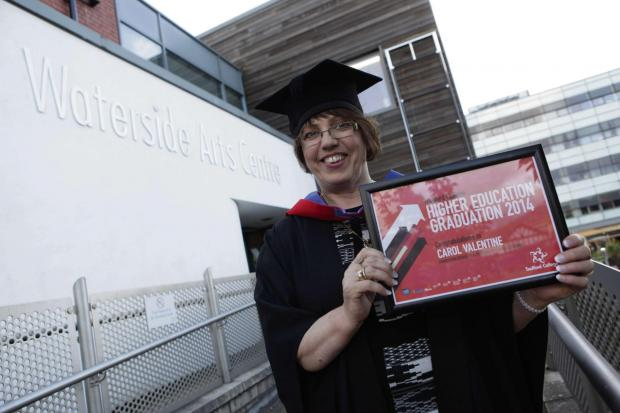 Carol proudly shows of her Foundation Degree certificate