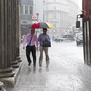 Members of the public get soaked as heavy rain falls in the City of London
