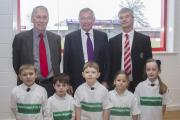 Sir Alex Ferguson, centre, flanked by Peter Foster, left, director of Altrincham FC Community Sports Trust, and Grahame Rowley, Altrincham FC chairman, with some youngsters from Stamford Park School in Hale at the opening of the community sports hall