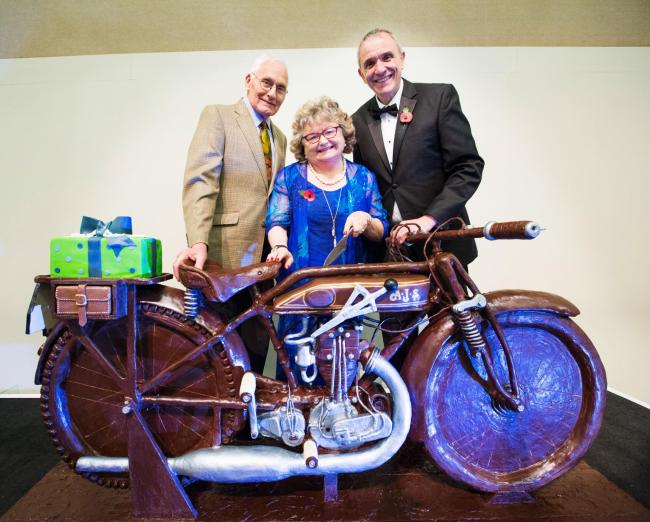 Carole Nash with David Newman (right), chief executive, and Ivan Rhodes, a policy holder with the company. His bike was the first to be insured by the firm and the cake is replica of it.