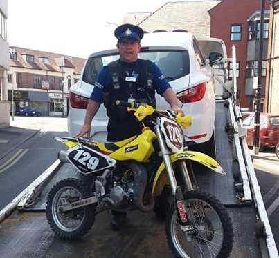 PCSO Stubbs pictured with the scrambler bike he seized in Sale. Image from GMP Trafford South Facebook page