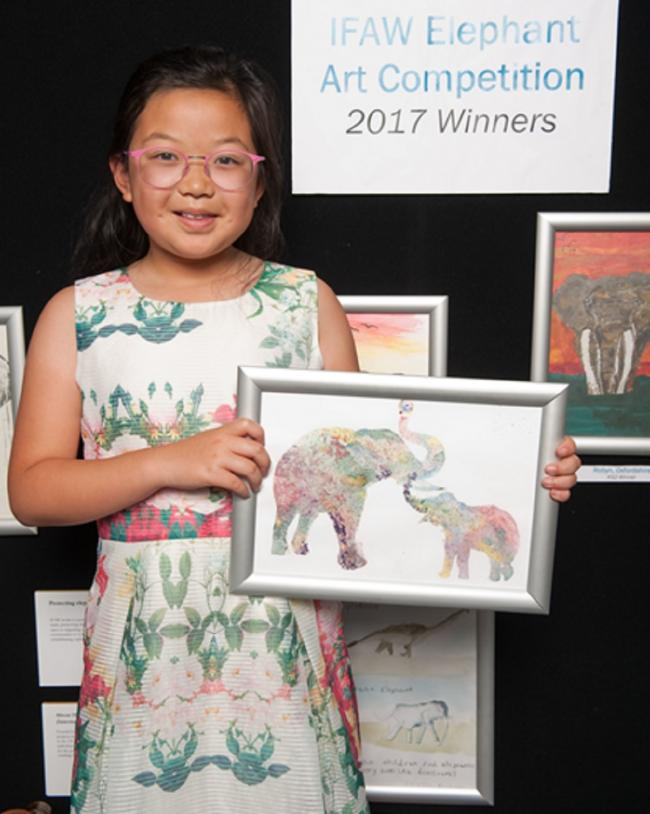 Withington Girls' School Junior pupil Siena Chae, aged 10, from Hale, shows off her prize-winning piece of work during a presentation at the Houses of Parliament, after winning a national art competition run by the International Fund for Animal Welfare.