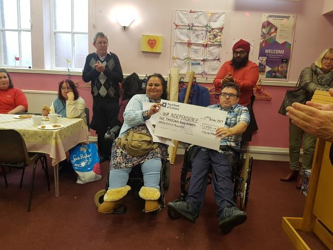 Renu Duggal and Colin Parker hold up Colin's cheque