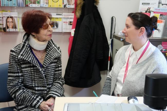Gail, one of Henshaws' patient support officers in Manchester Royal Eye Hospital, talking to a Henshaws service user, Marion
