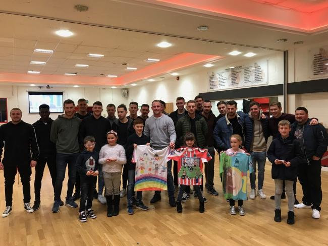 The youngsters with their winning shirt designs, l ro r Joseph Slater Snape, 10, Holly Sachro, seven, and Emily Bennett, aged six. The first team squad members are looking on