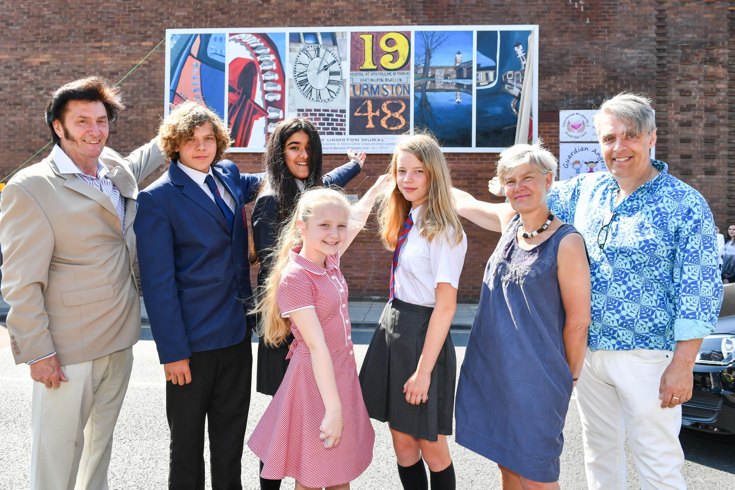 Urmston in Bloom: Kevin Murphy (left) and pupils from local schools and colleges joined Kate Green, MP for Stretford & Urmston, and Neil Roland (right) at the unveiling of the Urmston Mural.