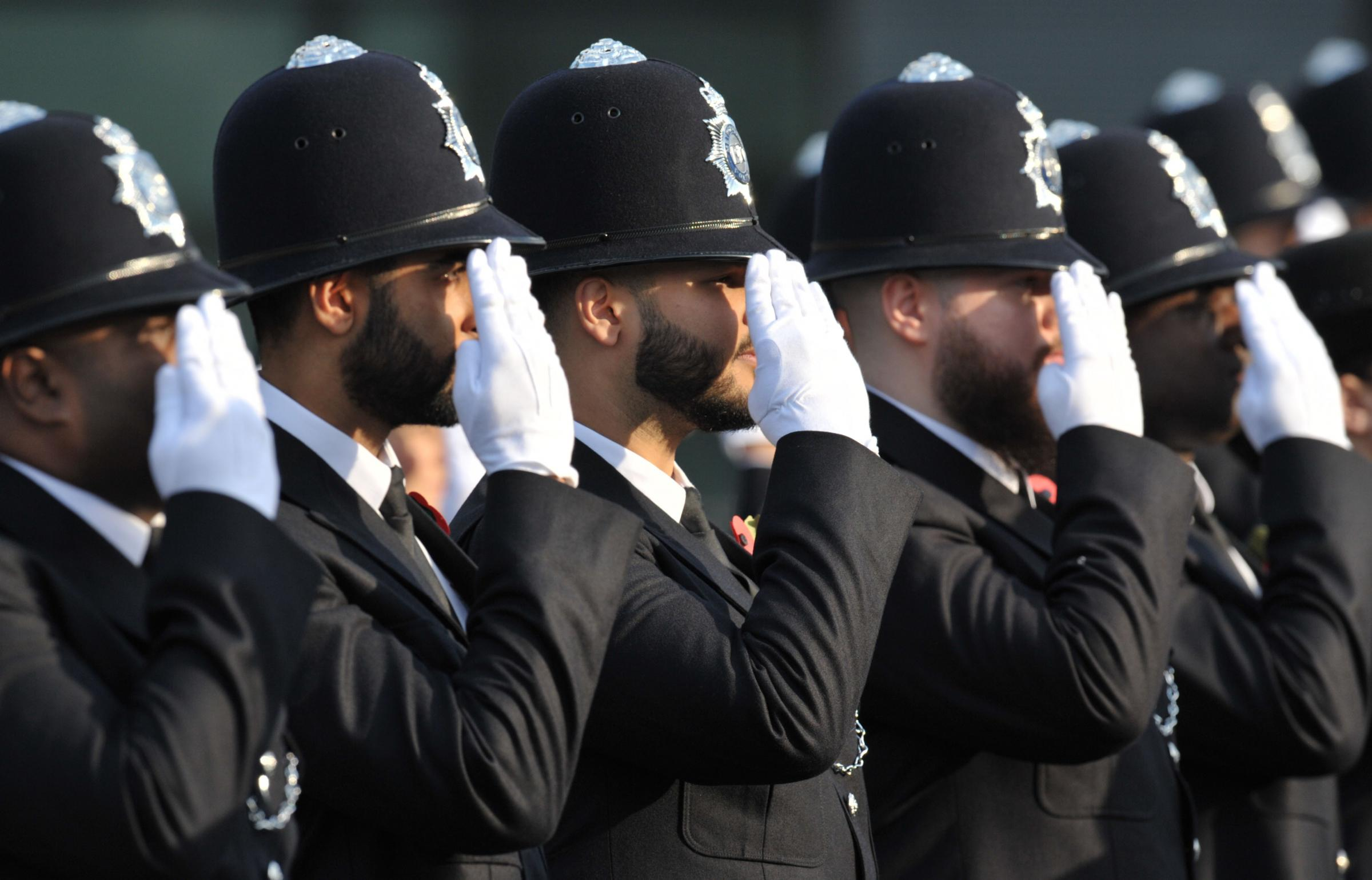 Police recruits saluting during a passing out parade for new officers.
