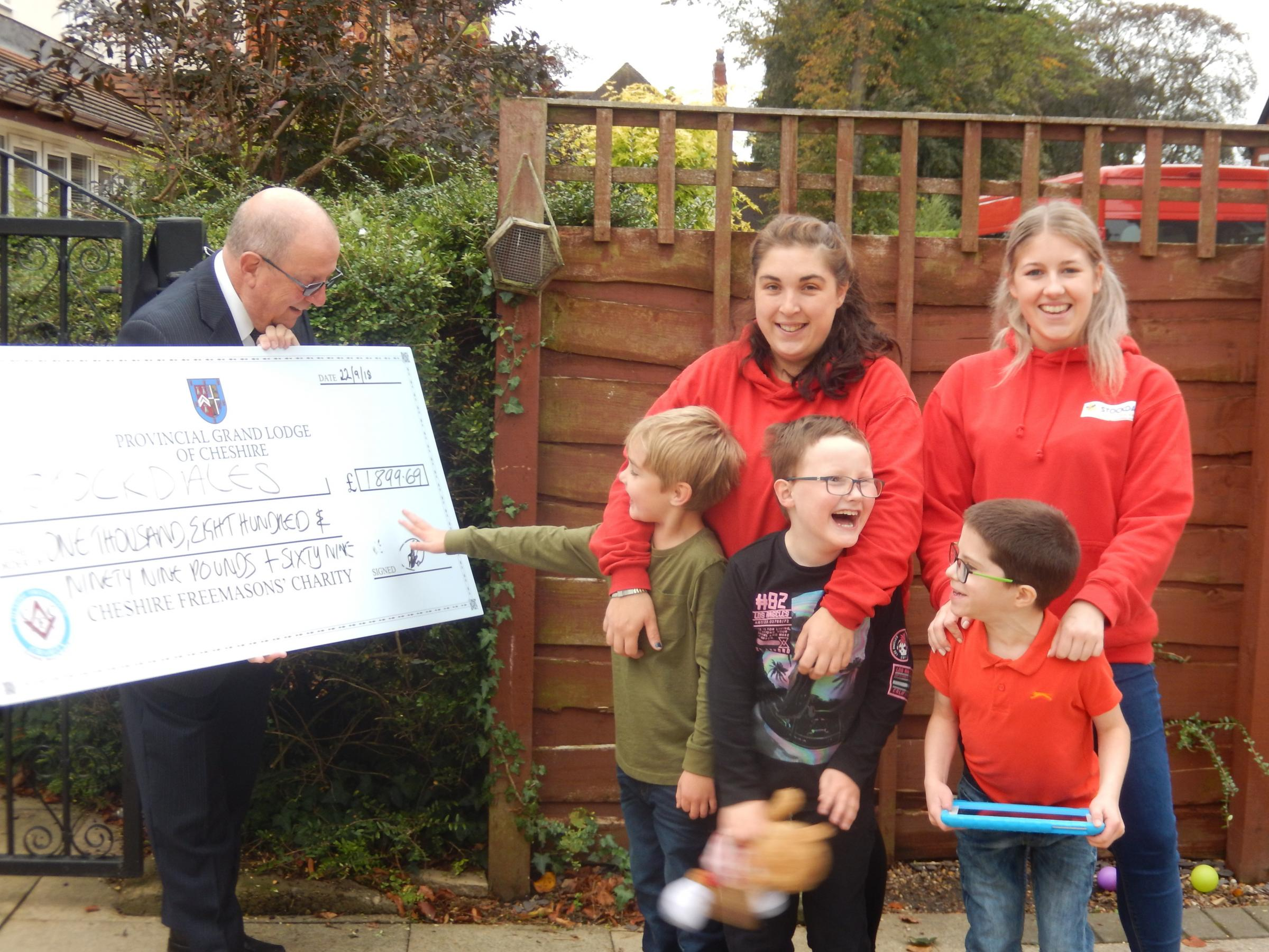 Freemason Keith Howbrigg presents a cheque for nearly £2,000 to Stockdales volunteers Danielle Collier and Molly Taylor, alongside Efe, Thomas and Joshua.