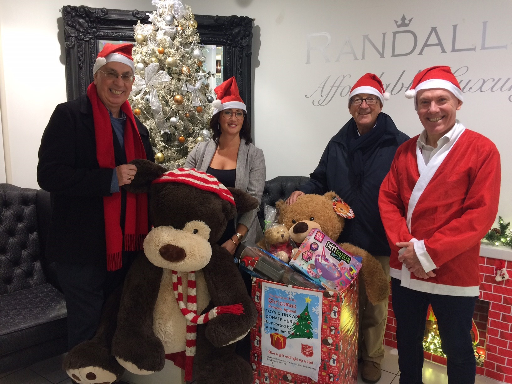 From left, Ken Garrity, Altrincham Rotary Club; Barney the dog;  Sonia Stanley, Randalls; Brian Soper, Altrincham Rotary Club; and Martin Duff, owner Randalls Jewellers; with some of the toys and tins already donated.